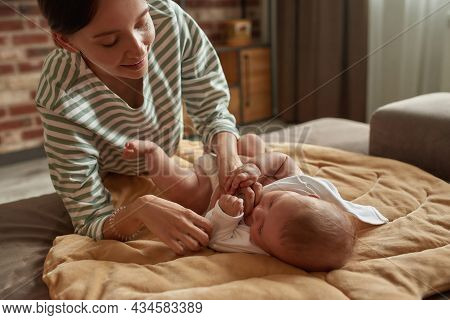Close Portrait Of Tender And Caring Mother Dressing Her Cute Infant Baby, Lying On Couch Covered Wit