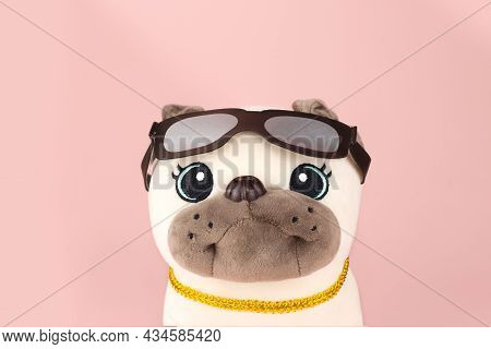 Plush Soft Light Beige Pug Dog Toy With Glasses And Gold Collar Isolated On Pink Background. Portrai