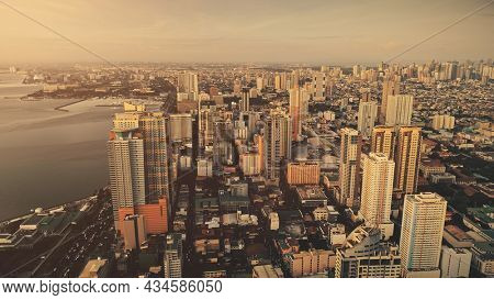 Slow motion skyscrapers cityscape at ocean bay aerial. Metropolis port city sun light landscape. Philippines capital town of Manila at sunlight summer day. Downtown buildings at sea gulf
