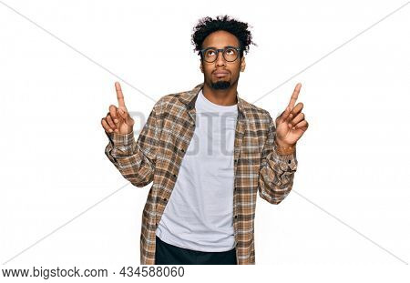 Young african american man with beard wearing casual clothes and glasses pointing up looking sad and upset, indicating direction with fingers, unhappy and depressed.
