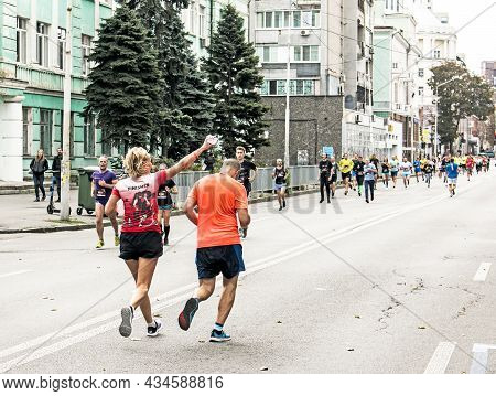 Residents Of The City At The Marathon Race. Volunteers Distribute Water And Water The Runners.