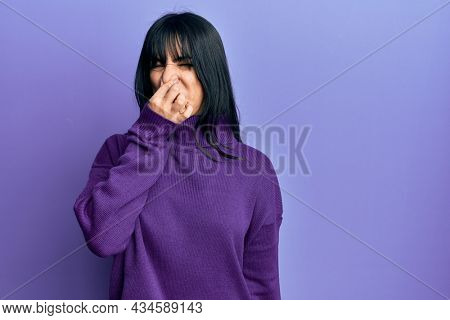 Young brunette woman with bangs wearing turtleneck sweater smelling something stinky and disgusting, intolerable smell, holding breath with fingers on nose. bad smell
