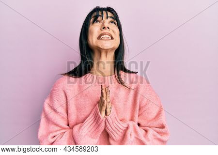 Young brunette woman with bangs wearing casual winter sweater begging and praying with hands together with hope expression on face very emotional and worried. begging.
