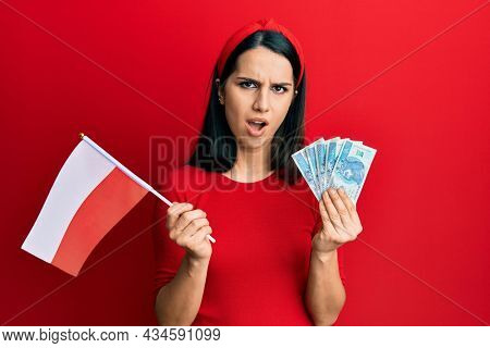 Young hispanic woman holding poland flag and zloty banknotes in shock face, looking skeptical and sarcastic, surprised with open mouth