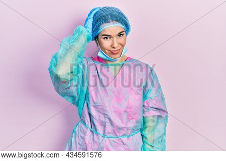 Young brunette woman wearing surgeon uniform and medical mask confuse and wonder about question. uncertain with doubt, thinking with hand on head. pensive concept.