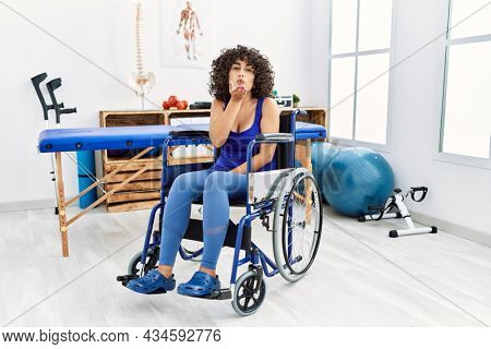 Young middle eastern woman sitting on wheelchair at physiotherapy clinic looking at the camera blowing a kiss with hand on air being lovely and sexy. love expression.