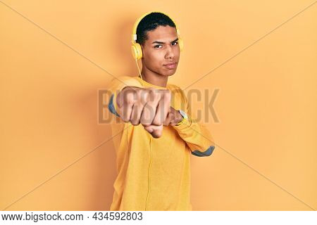 Young african american guy listening to music using headphones punching fist to fight, aggressive and angry attack, threat and violence