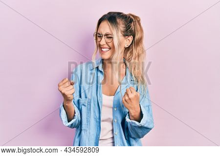 Beautiful young blonde woman wearing casual clothes and glasses excited for success with arms raised and eyes closed celebrating victory smiling. winner concept.