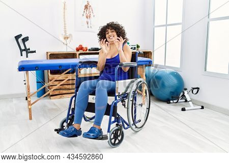 Young middle eastern woman sitting on wheelchair at physiotherapy clinic disgusted expression, displeased and fearful doing disgust face because aversion reaction. with hands raised