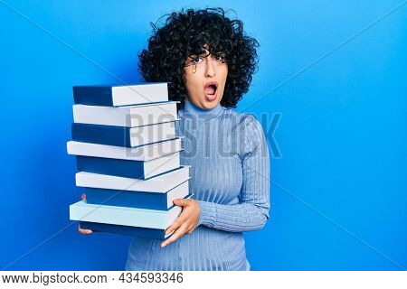 Young middle east woman holding a pile of books in shock face, looking skeptical and sarcastic, surprised with open mouth