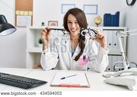 Young doctor woman holding optometry glasses and normal glasses winking looking at the camera with sexy expression, cheerful and happy face.