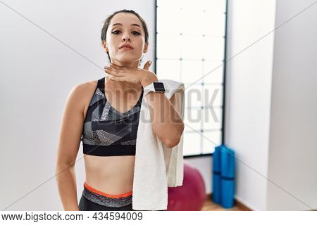Young brunette woman wearing sportswear and towel at the gym cutting throat with hand as knife, threaten aggression with furious violence