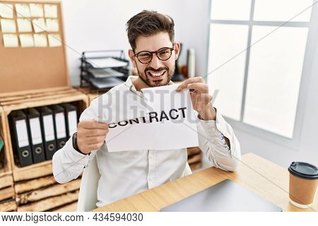 Young man with beard breaking contract paper at the office winking looking at the camera with sexy expression, cheerful and happy face.