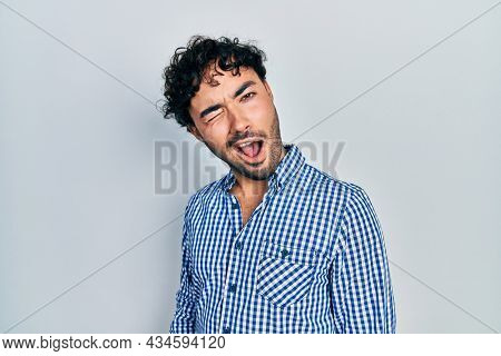 Young hispanic man wearing casual clothes winking looking at the camera with sexy expression, cheerful and happy face.