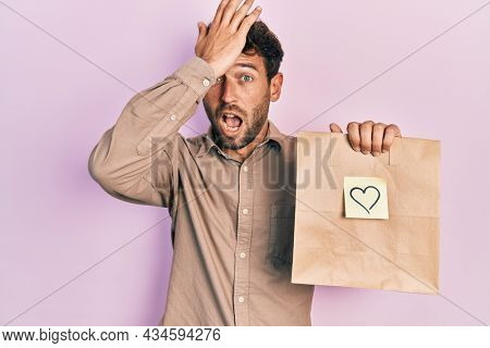 Handsome man with beard holding delivery paper bag with heart reminder surprised with hand on head for mistake, remember error. forgot, bad memory concept.