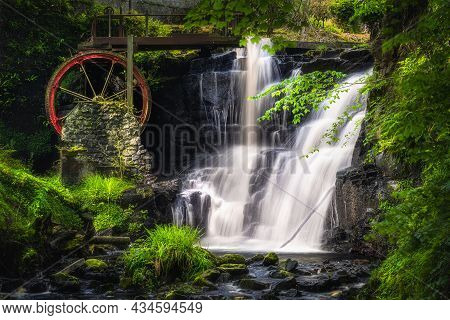 Vintage Red Waterwheel With Waterfall At Spring In Glenariff Forest Park, County Antrim, Northern Ir