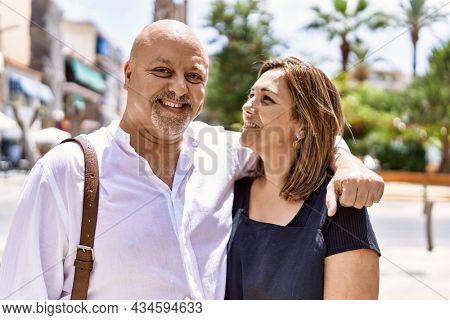 Middle age hispanic couple of husband and wife together on a sunny day outdoors. Smiling happy in love hugging at the city