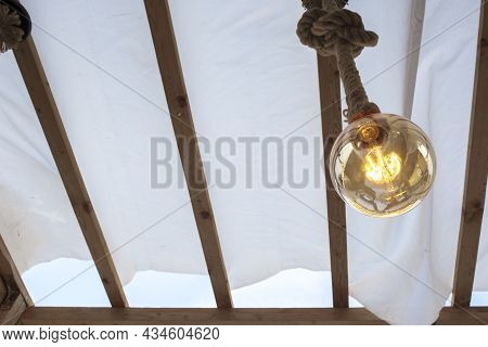 Rope Light Bulb Over Canvas Pergola Cover. Low Angle View
