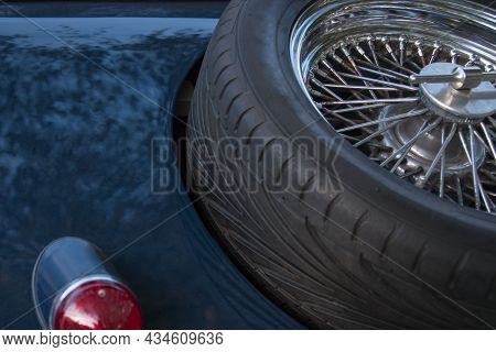 Partial Rear View Of Blue Vintage Car With Taillight And Spare Spoke Rim Wheel