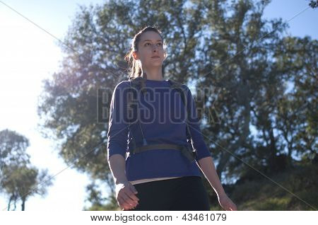 Frontal centered close up of woman hiking in blue shirt facing right
