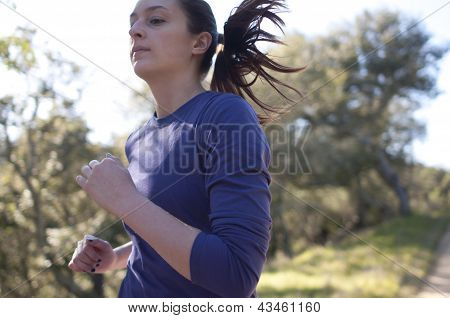 Very close up of woman jogging, facing left