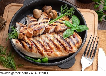 Roasted chicken fillet and mushrooms with herb in the frying pan on the wooden table close-up.