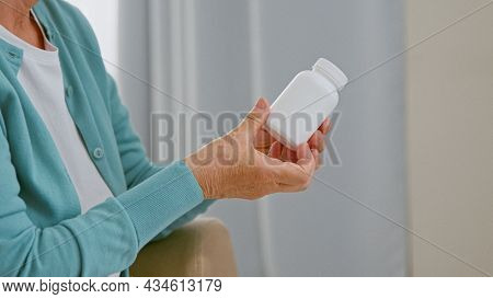 Mature woman patient takes blank white bottle of medicine from doctor sitting in comfortable armchair
