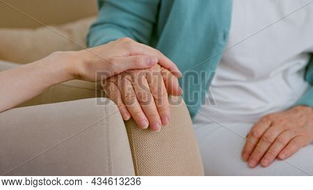 Caregiver cheers up senior lady patient touching hand while sits in armchairs in light room