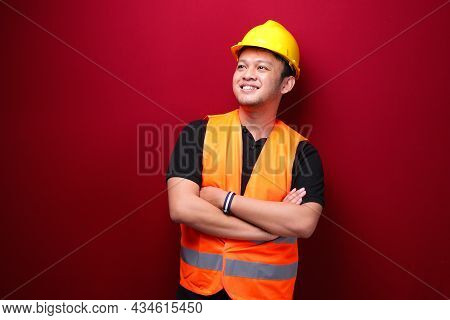 Portrait Of Smiling Young Asian Man Worker Isolated On Red.