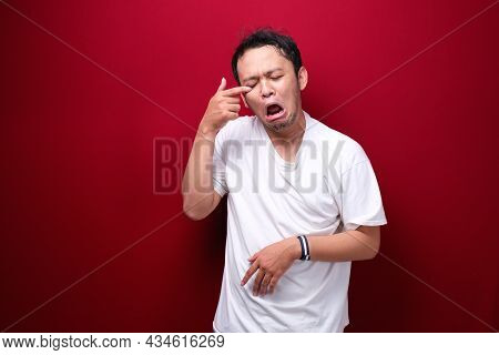 Crying Face Of Young Asian Man With Hand Gesture. Advertising Model Concept.