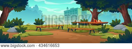 City Park With Wooden Picnic Table And Benches, Green Trees, Grass With Flowers And Town Buildings O