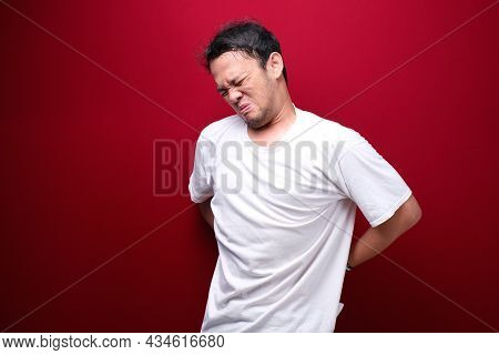 Sad And Upset Young Asian Man With Serious Pain In Back Man