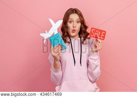 Portrait Of Excited Curly Haired Teenage Girl In Hoodie Showing Passport With Paper Airplane And Sal