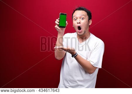 Shock Young Asian Man Pointing On Green Blank Space On Smartphone On Red Background.