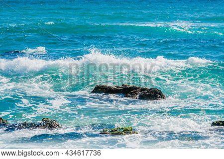 Waves Crashing To Shore Among Large Boulders On Sunny Morning.
