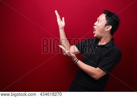 Young Asian Man Is Surprised And Shouting Wow With Pointing Right With His Hand Isolated On Red Back