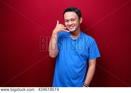 Smiling Young Asian Man With Talk Or Call Gesture Hand