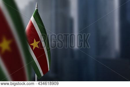Small Flags Of Suriname On A Blurry Background Of The City
