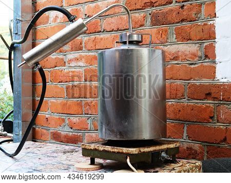 Moonshine Still Standing On An Old Heating Plate Against A Brick Wall Background, Production Of Alco