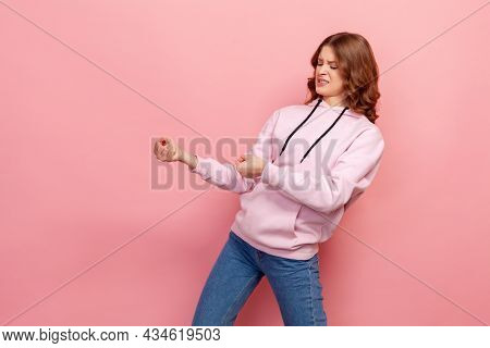 Portrait Of Concentrated Teen Girl In Hoodie Holding Invisible Rope And Pulling Something Heavy, Loo