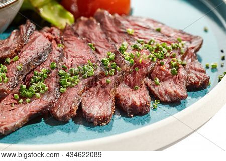 Roast beef with vegetables and sauce on trendy plate. Sliced meat steak roast grill with tomatoes and broccoli isolated on white table. Angus roast beef in healthy style for restaurant