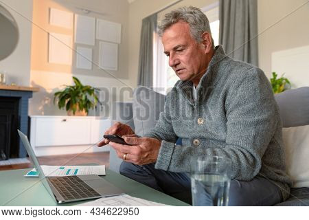 Focused caucasian senior man sitting on sofa, doing paperwork, using smartphone and laptop. active retirement lifestyle at home.