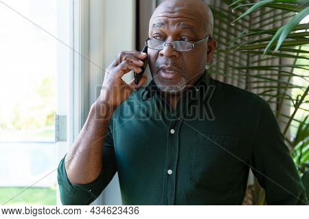 Thoughtful african american senior man having call and looking outside window. retirement lifestyle and relaxing at home.