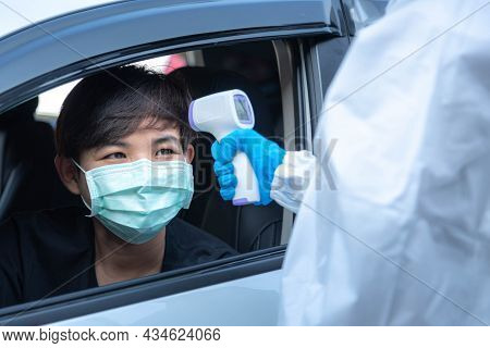 Medical Staff With Ppe Use Infrared Thermometer Gun To Check Body Temperature At Drive Thru Station