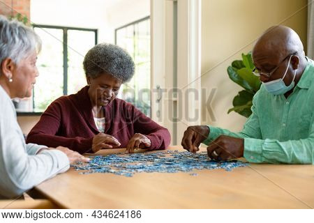 Two diverse senior women and african american male friend wearign face mask doing puzzles. socialising with friends at home.