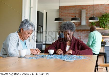 Two diverse female friends sitting in kitchen with coffee and doing puzzles. socialising with friends at home.