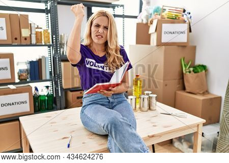 Beautiful blonde woman wearing volunteer t shirt at donations stand taking notes annoyed and frustrated shouting with anger, yelling crazy with anger and hand raised