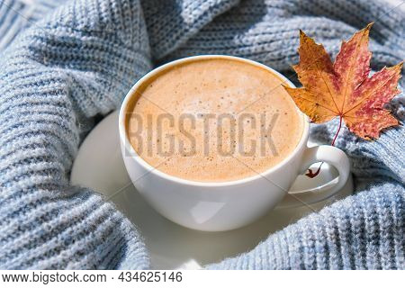 White Cup Of Morning Warming Coffee On Blue Knitted Sweater With Maple Yellow Leaves Background. Coz