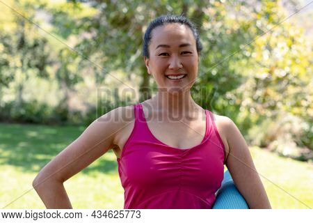 Happy fit korean woman holding yoga mat and looking at camera. fitness and healthy, active lifestyle.