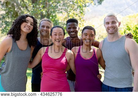Group of happy fit diverse female and male friends holding yoga mats and taking selfie. fitness and healthy, active lifestyle.